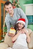Bella giovane donna che guarda il contenitore di regalo e che sorride mentre il suo ragazzo fotografia stock libera da diritti