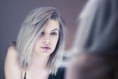 Bella giovane donna che guarda nello specchio Immagini Stock Libere da Diritti