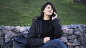 Bella giovane donna che ha una conversazione telefonica in un parco stock footage