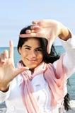 Bella giovane donna che incornicia il suo fronte Fotografia Stock Libera da Diritti