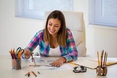 Bella giovane donna che lavora all'ufficio con un compa del disegno fotografia stock