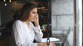 Bella giovane donna che lavora con il computer portatile e che parla sullo smartphone che parla con cliente che si siede vicino a video d archivio