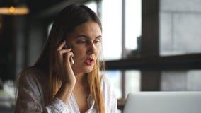 Bella giovane donna che lavora con il computer portatile e che parla sullo smartphone che parla con cliente che si siede vicino a archivi video