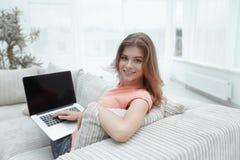 Bella giovane donna che lavora con il computer portatile che si siede sul sofà e che esamina macchina fotografica Immagine Stock