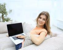 Bella giovane donna che lavora con il computer portatile che si siede sul sofà e che esamina macchina fotografica Fotografia Stock Libera da Diritti