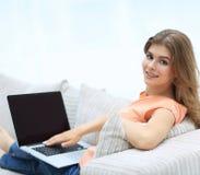 Bella giovane donna che lavora con il computer portatile che si siede sul sofà e che esamina macchina fotografica Fotografie Stock
