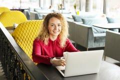 Bella giovane donna che lavora a distanza sul suo computer portatile alla moda alla caffetteria dei pantaloni a vita bassa Free l immagine stock