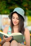 Bella giovane donna che legge un libro fuori Fotografie Stock