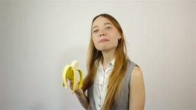 Bella giovane donna che mangia banana archivi video