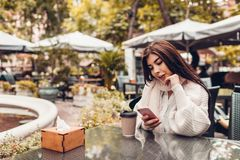 Bella giovane donna che mangia caffè in caffè all'aperto mentre per mezzo dello smartphone Ritratto del messaggio di battitura a  fotografie stock libere da diritti