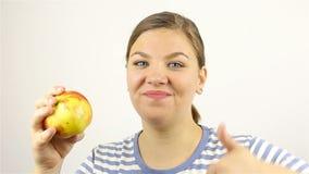 Bella giovane donna che mangia una mela rossa archivi video