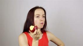 Bella giovane donna che mangia una mela rossa stock footage