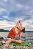 Bella giovane donna che medita nella posa di yoga su fiume vicino di pietra Immagini Stock Libere da Diritti