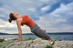 Bella giovane donna che medita nella posa di yoga su fiume vicino di pietra Fotografie Stock