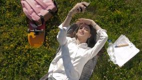 Bella giovane donna che mette sull'erba e che ascolta la musica Fabbricazione del selfie video d archivio