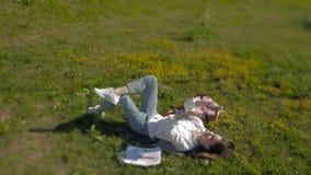 Bella giovane donna che mette sull'erba e che ascolta la musica Fabbricazione del selfie archivi video