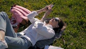 Bella giovane donna che mette sull'erba e che ascolta la musica Fabbricazione del selfie stock footage