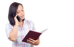 Bella giovane donna che parla sul telefono cellulare e che controlla la sua D Fotografia Stock Libera da Diritti