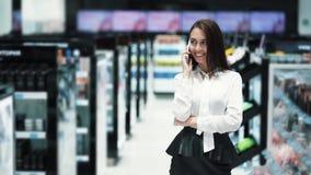Bella giovane donna che parla sul telefono e che compera nel deposito cosmetico archivi video