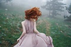 Bella giovane donna che passa la montagna in un vestito lungo, natura fotografie stock libere da diritti