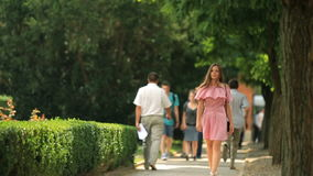 Bella giovane donna che passeggia in un parco sola all'estate mentre l'altra gente che cammina da lei archivi video