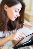 Bella giovane donna che per mezzo del computer digitale della compressa Immagini Stock Libere da Diritti