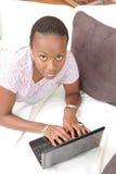 Bella giovane donna che per mezzo del computer portatile Fotografie Stock Libere da Diritti