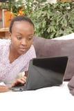 Bella giovane donna che per mezzo del computer portatile Immagine Stock