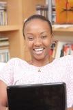 Bella giovane donna che per mezzo del computer portatile Fotografie Stock
