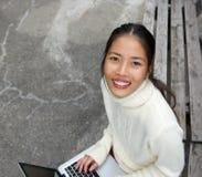 Bella giovane donna che per mezzo del computer portatile all'aperto Immagine Stock