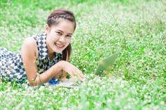 Bella giovane donna che per mezzo del computer portatile che si trova al prato Fotografie Stock Libere da Diritti