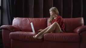 Bella giovane donna che per mezzo del suo computer portatile ed esaminando macchina fotografica con il sorriso mentre sedendosi s video d archivio