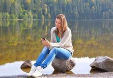 Bella giovane donna che per mezzo dello smartphone vicino ad un lago Fotografie Stock Libere da Diritti
