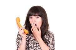 Bella giovane donna che per mezzo di retro telefono arancio Fotografie Stock
