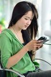 Bella giovane donna che per mezzo di un telefono mobile Immagine Stock