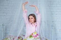 Bella giovane donna che porta camicia rosa, allungando le sue armi, sedentesi sul letto Immagine Stock