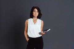 Bella giovane donna che posa sopra il fondo grigio e che tiene taccuino in mani Fotografia Stock Libera da Diritti