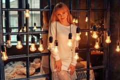 Bella giovane donna che posa sul letto, la luce calda dalle lampade immagini stock