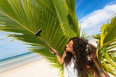 Bella giovane donna che prende selfie con il bastone del selfie sulla spiaggia Fotografie Stock