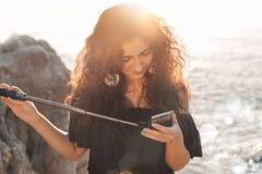 Bella giovane donna che prende selfie sulla spiaggia al tramonto Immagini Stock