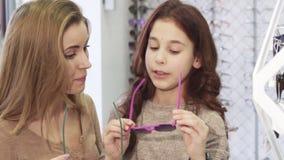 Bella giovane donna che prova sugli occhiali da sole con la sua sorellina sveglia archivi video