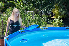 Bella giovane donna che pulisce una piscina piegante con la SK fotografia stock libera da diritti