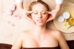 Bella giovane donna che riceve massaggio facciale Fotografie Stock Libere da Diritti
