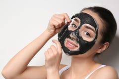 Bella giovane donna che rimuove maschera nera dal suo fronte su bianco fotografia stock libera da diritti