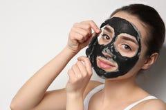 Bella giovane donna che rimuove maschera nera dal suo fronte fotografia stock libera da diritti