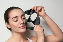 Bella giovane donna che rimuove maschera nera dal suo fronte fotografie stock
