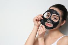 Bella giovane donna che rimuove maschera nera dal suo fronte su fondo bianco immagine stock