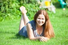 Bella giovane donna che riposa sul prato inglese verde Fotografia Stock