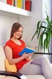 Donna che riposa sul sofà e che legge il libro Immagini Stock