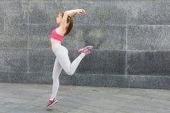 Bella giovane donna che salta contro la parete grigia Immagini Stock